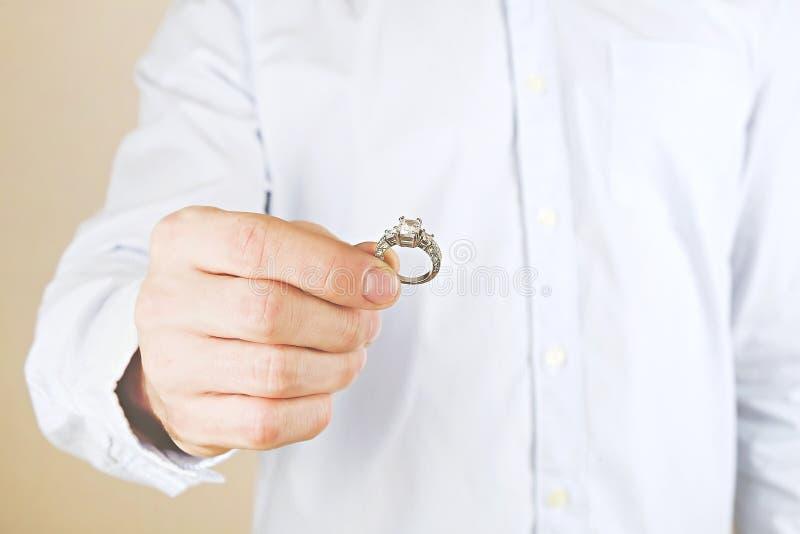 Verpflichtungs-/Heirat-/Heiratsantragszene Schließen Sie oben vom Mann, der seiner Braut den teuren Goldplatin-Diamantring übergi lizenzfreies stockfoto