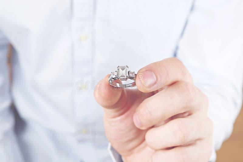 Verpflichtungs-/Heirat-/Heiratsantragszene Schließen Sie oben vom Mann, der seiner Braut den teuren Goldplatin-Diamantring übergi stockfotografie