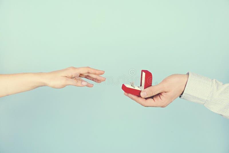 Verpflichtungs-/Heirat-/Heiratsantragszene Schließen Sie oben vom Mann, der seiner Braut den teuren Goldplatin-Diamantring übergi stockfoto