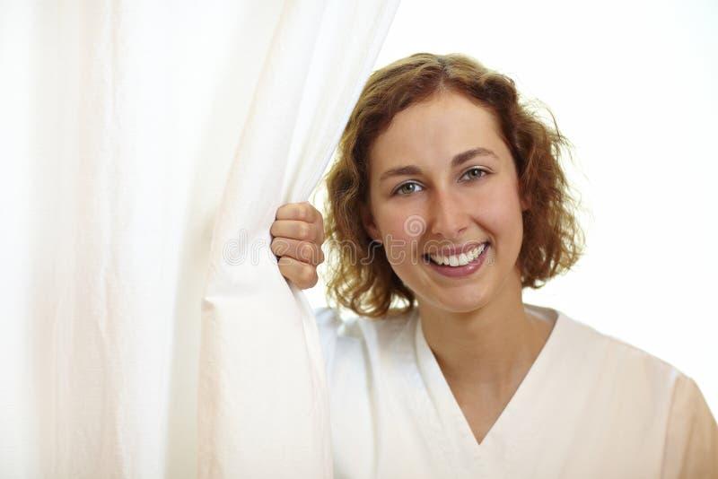 Verpleegster achter gordijn royalty-vrije stock afbeeldingen
