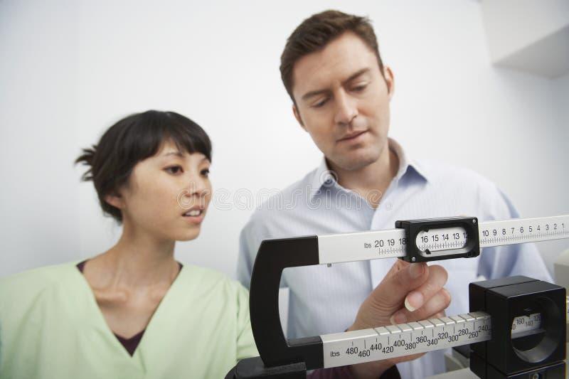 Verpleegster Adjusting Weighing Scale voor de Mens royalty-vrije stock foto
