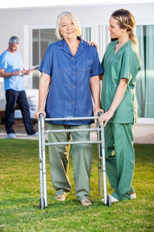 Verpleegster Assisting Senior Woman om met Zimmer te lopen royalty-vrije stock afbeeldingen