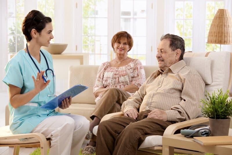 Verpleegster die aan bejaarde patiënten thuis spreken stock afbeeldingen