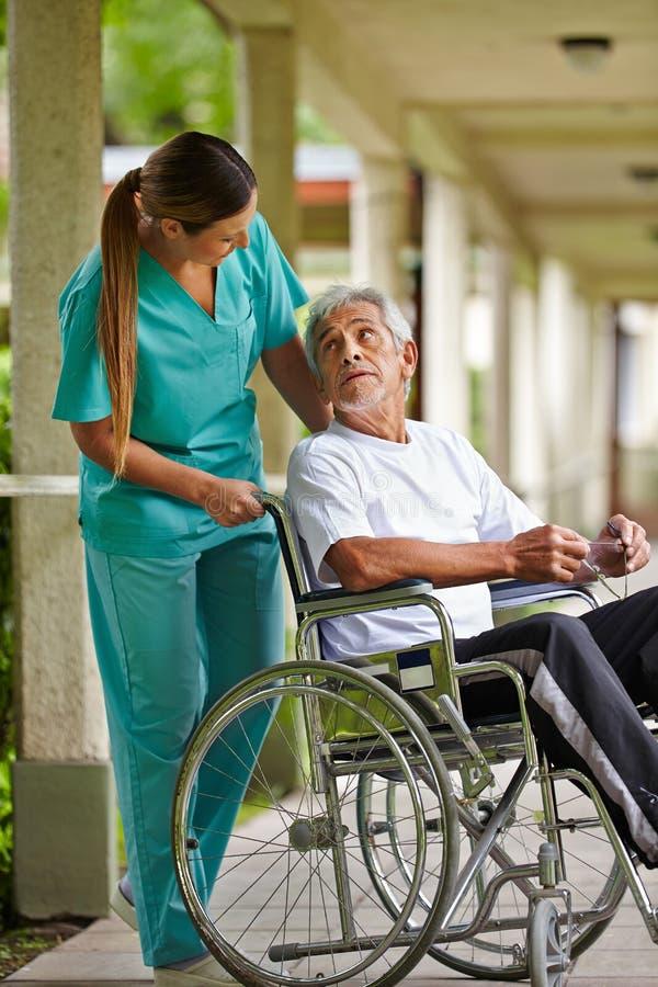 Verpleegster die aan bejaarde spreken royalty-vrije stock fotografie