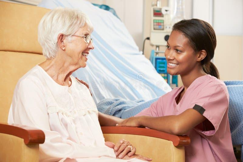 Verpleegster die aan Hogere Vrouwelijke Patiënt Gezet als Voorzitter spreken stock afbeelding