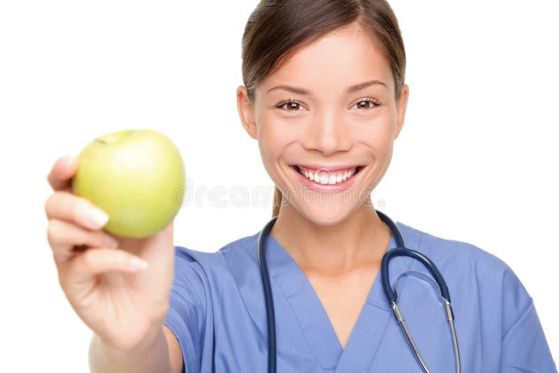 Verpleegster die appel geeft royalty-vrije stock fotografie