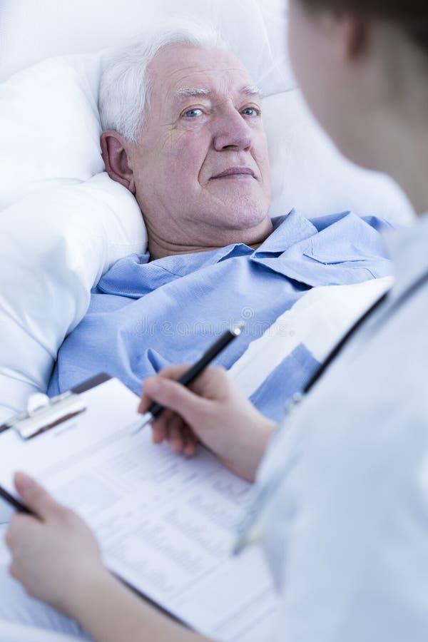 Verpleegster die bejaarde patiënt interviewen stock afbeeldingen