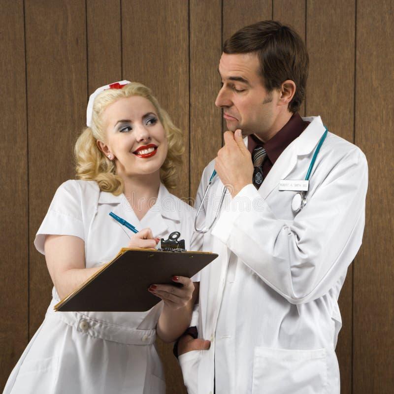 Verpleegster die bij arts glimlacht. royalty-vrije stock afbeelding