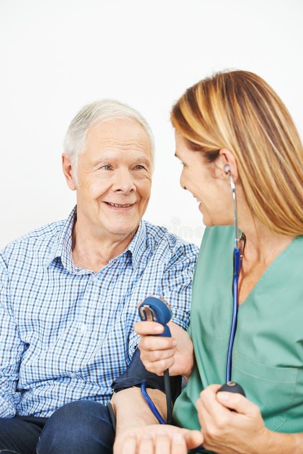Verpleegster die bloeddruk controle doen royalty-vrije stock afbeeldingen