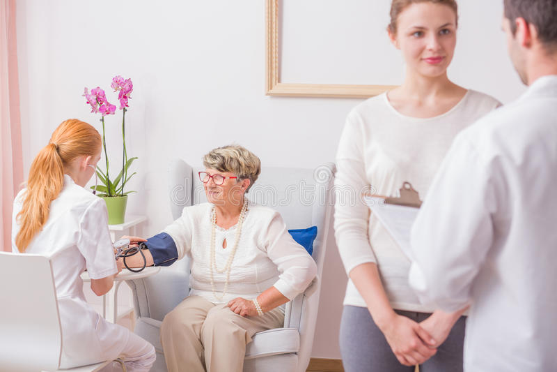 Verpleegster die bloeddruk controleert stock foto