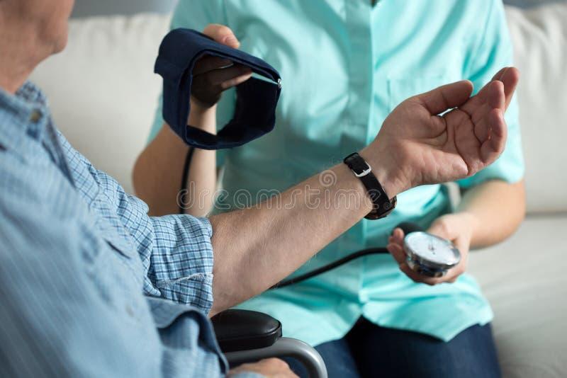 Verpleegster die bloeddruk meet stock foto