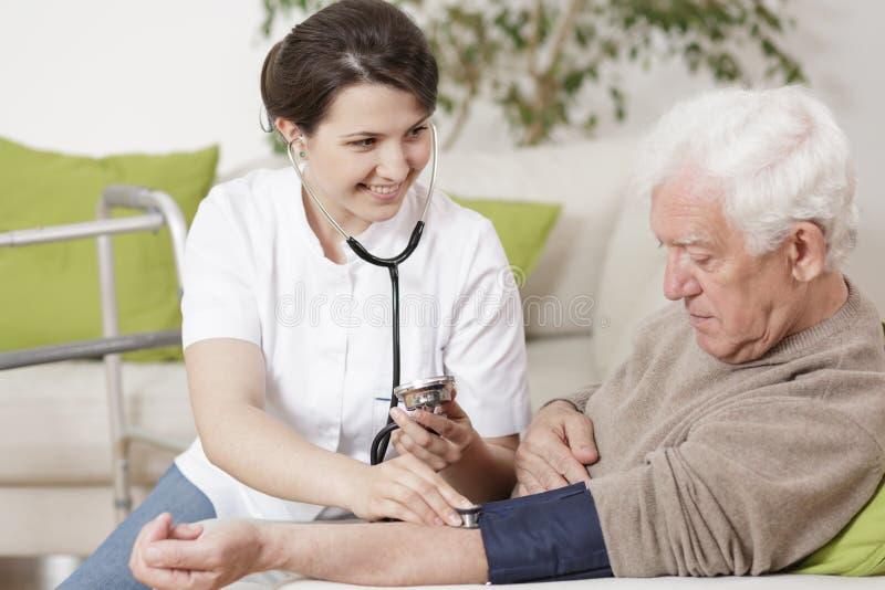 Verpleegster die bloeddruk meet stock fotografie