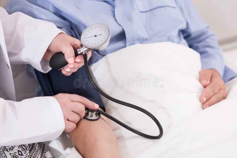 Verpleegster die bloeddruk meet stock afbeeldingen