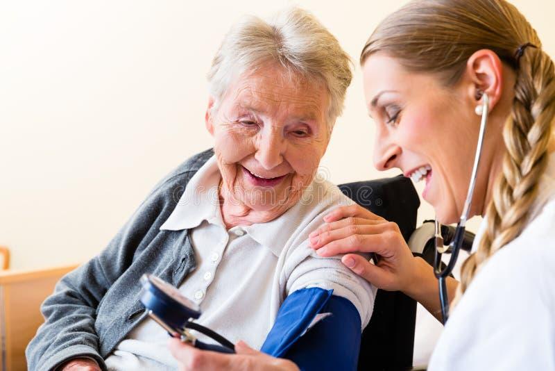 Verpleegster die bloeddruk meten bij hogere patiënt stock afbeeldingen