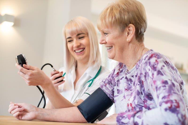 Verpleegster die bloeddruk van hogere vrouw thuis meet royalty-vrije stock afbeelding