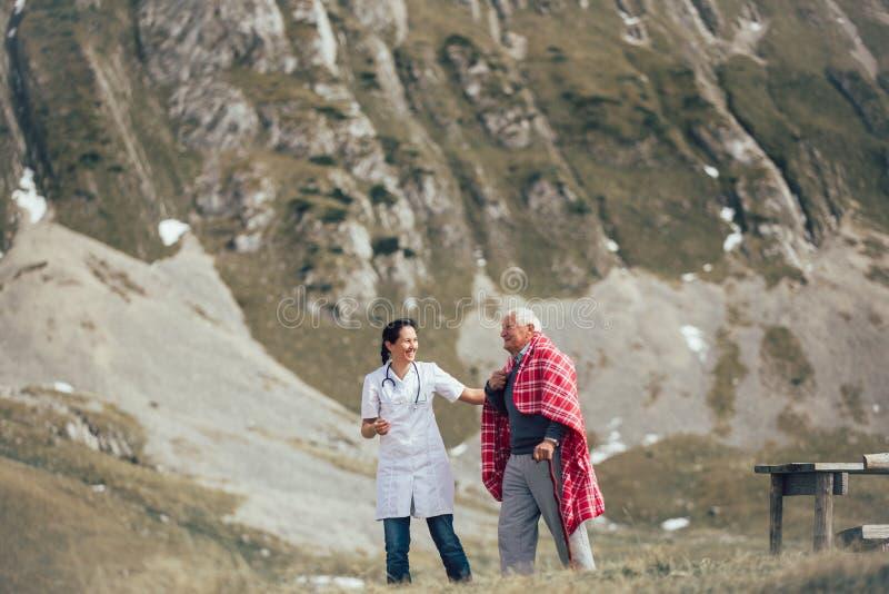 Verpleegster die de bejaarde hogere mens helpen om op frashlucht te lopen stock foto's