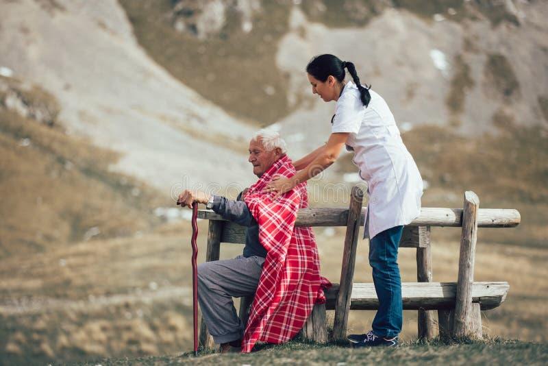 Verpleegster die de bejaarde hogere mens helpen om op frashlucht te lopen stock fotografie