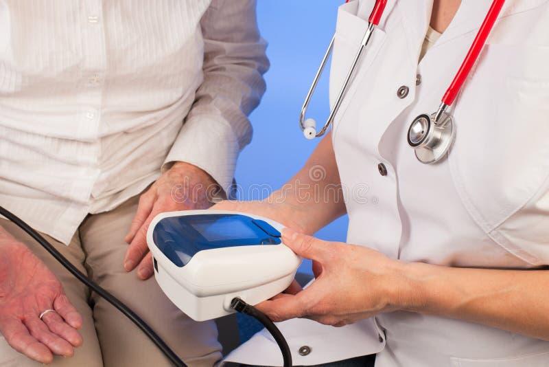 Verpleegster die de bloeddruk van een hogere vrouw meten royalty-vrije stock foto