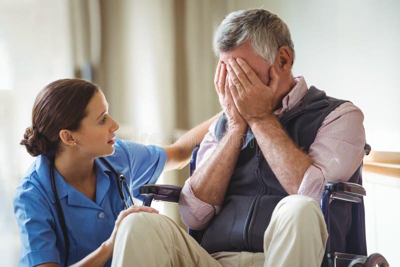 Verpleegster die de droevige hogere mens behandelen stock afbeelding