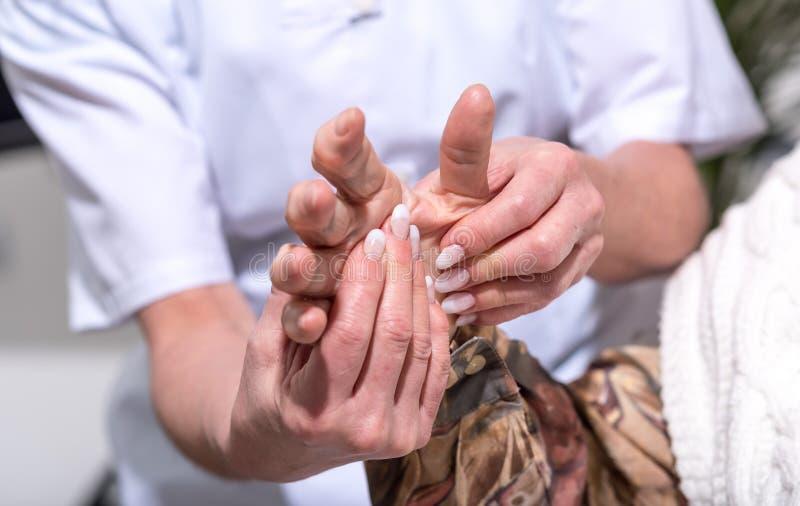 Verpleegster die de hand van een oude vrouw masseren royalty-vrije stock foto's