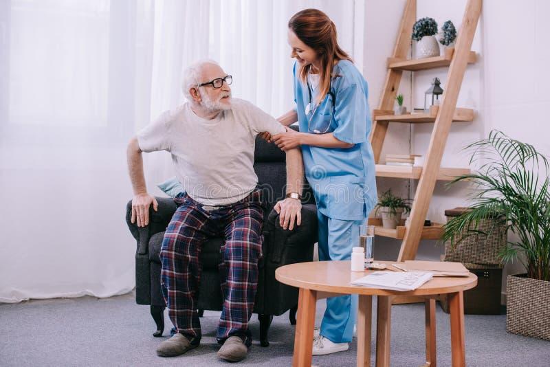 Verpleegster die de hogere mens helpen aan royalty-vrije stock afbeelding