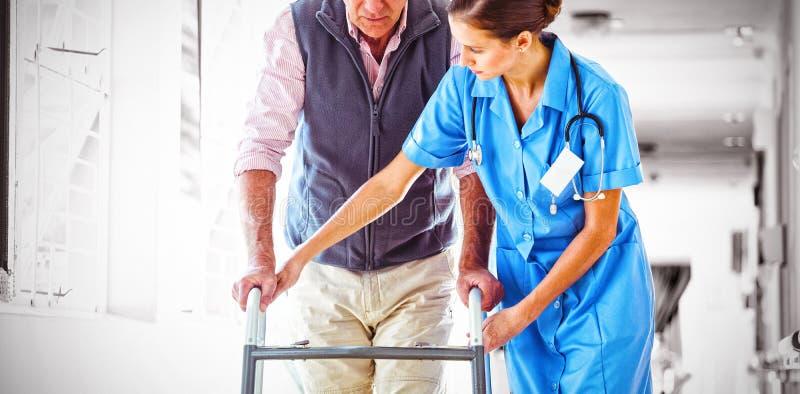 Verpleegster die de hogere mens met het lopen hulp helpen royalty-vrije stock foto