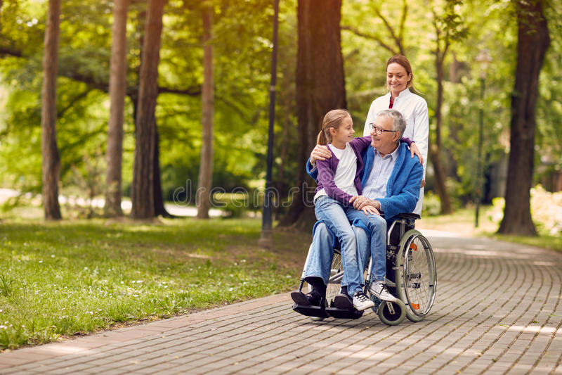 Verpleegster die de hogere mens op rolstoel met zijn jonge granddaugh duwen stock foto's