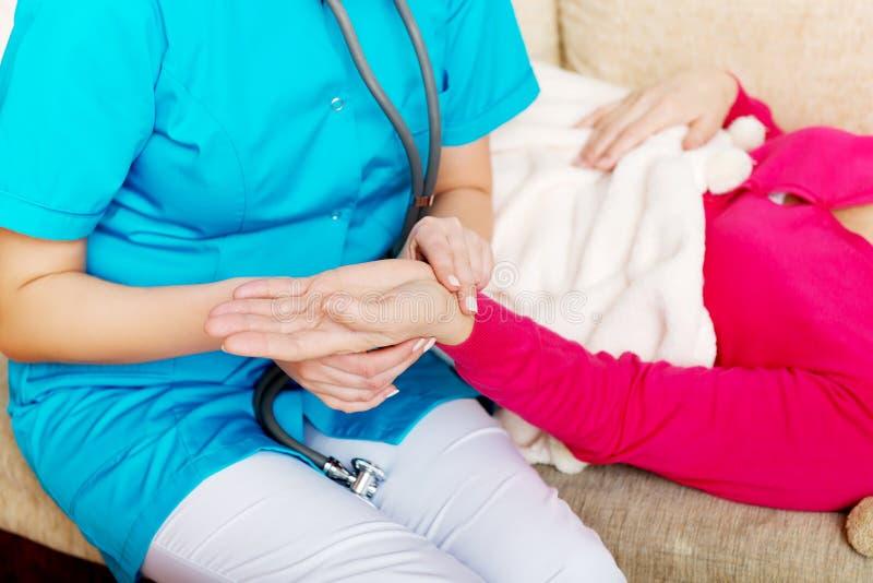 Verpleegster die de impuls van haar patiënt thuis nemen stock fotografie