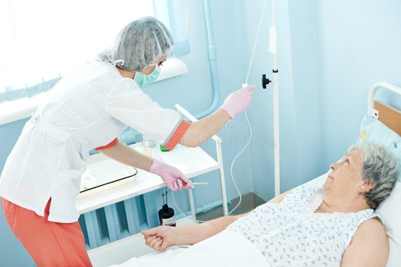 Verpleegster die druppelbuisje voor intraveneuze injectie voorbereiden stock foto