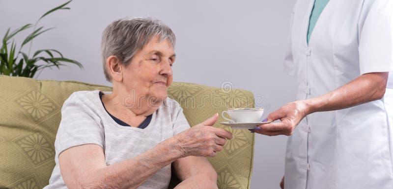 Verpleegster die een bejaarde persoon behandelen stock afbeeldingen