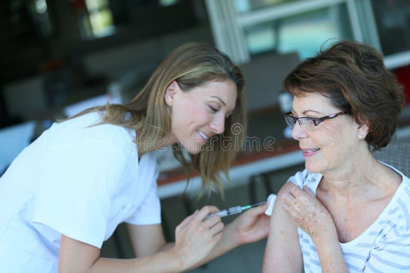 Verpleegster die een inenting geven aan een hogere vrouw stock foto's