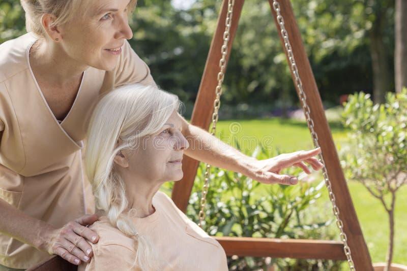 Verpleegster die een oudste in een tuin behandelen stock afbeeldingen