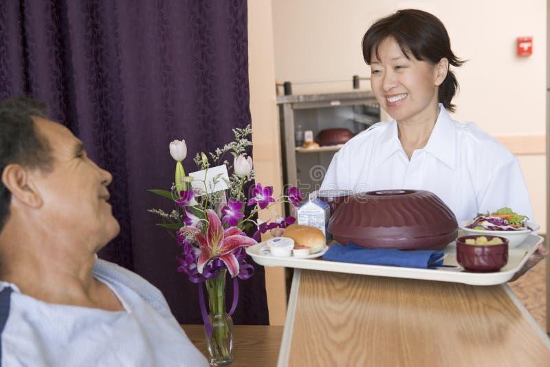 Verpleegster die een Patiënt dient een Maaltijd in Zijn Bed stock foto's