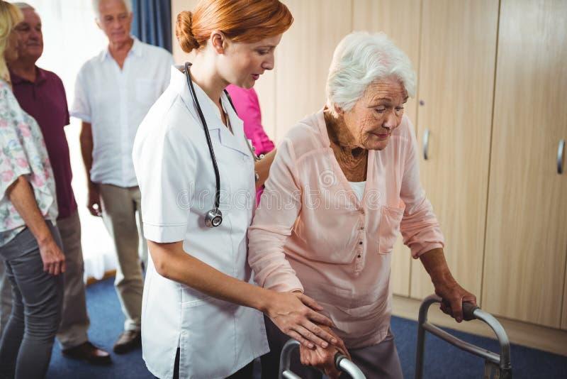 Verpleegster die een teruggetrokken vrouw helpen te lopen stock afbeeldingen