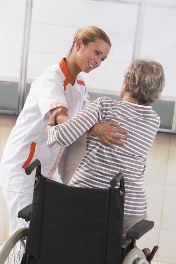 Verpleegster die gehandicapt bejaarde helpen opstaan royalty-vrije stock foto's
