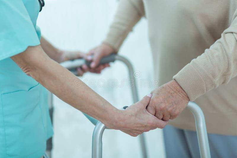 Verpleegster die gehandicapte bejaarde dame helpen stock afbeeldingen