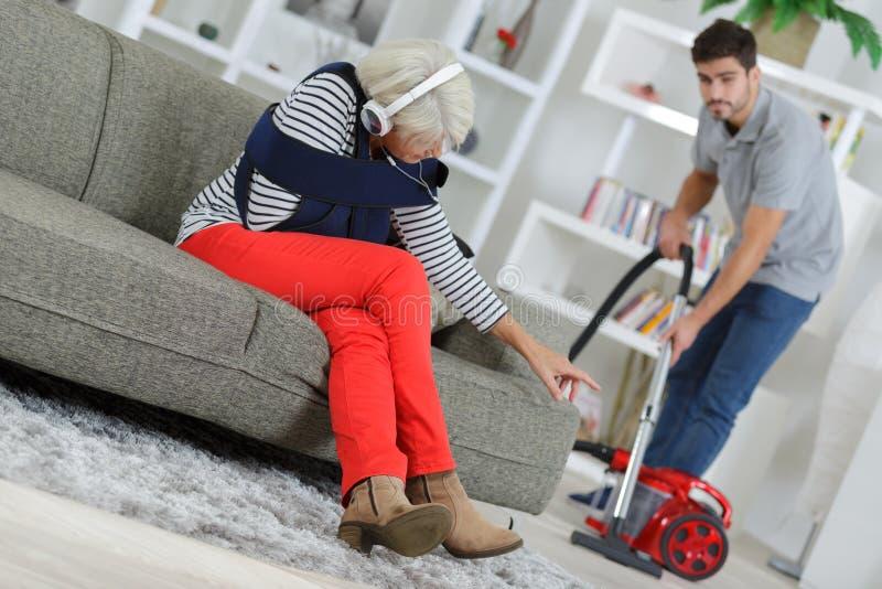 Verpleegster die gehandicapte vrouw met het schoonmaken van huis helpen stock foto