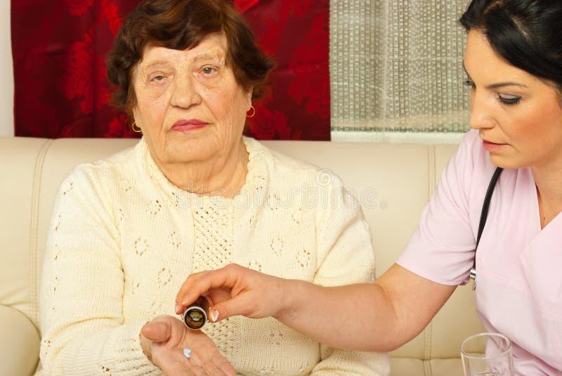 Verpleegster die geneesmiddelen geeft aan bejaarde stock fotografie