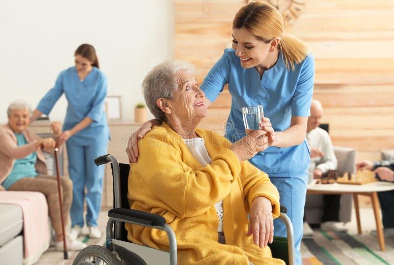 Verpleegster die glas water geven aan bejaarde in rolstoel bij pensioneringshuis stock afbeeldingen
