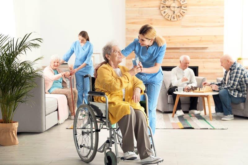 Verpleegster die glas water geven aan bejaarde in rolstoel Bijwonende hogere mensen stock afbeelding