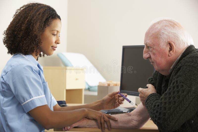 Verpleegster die hogere mannelijke patiënt inspuiten stock afbeelding