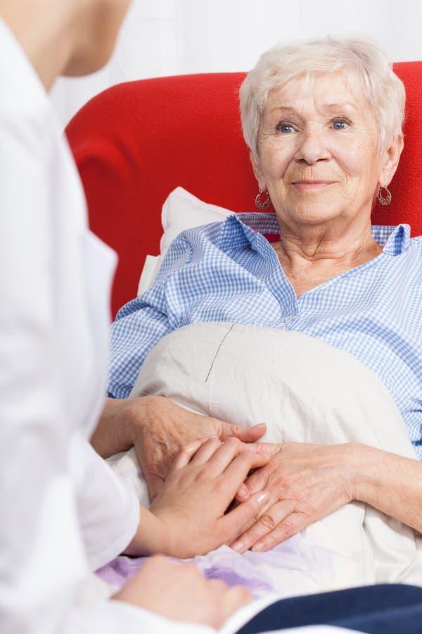 Verpleegster die hogere patiënt bezoeken stock afbeeldingen