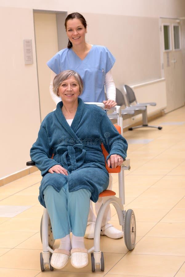 Verpleegster die hogere patiënt in rolstoel duwen stock afbeeldingen