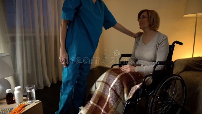 Verpleegster die hogere vrouw in de hulp en de hulp van de wielstoel in verpleeghuis troosten stock fotografie