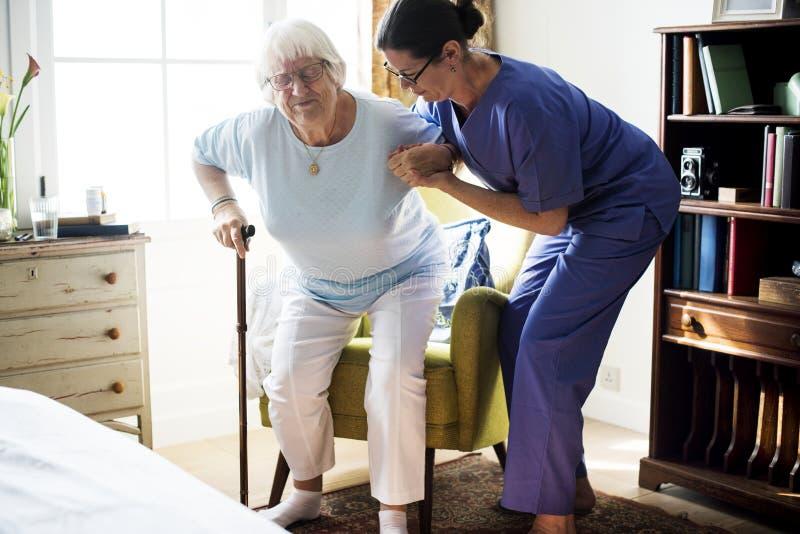 Verpleegster die hogere vrouw helpen zich te bevinden stock afbeelding