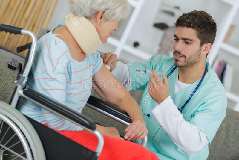 Verpleegster die injectie thuis geven aan bejaarde stock fotografie