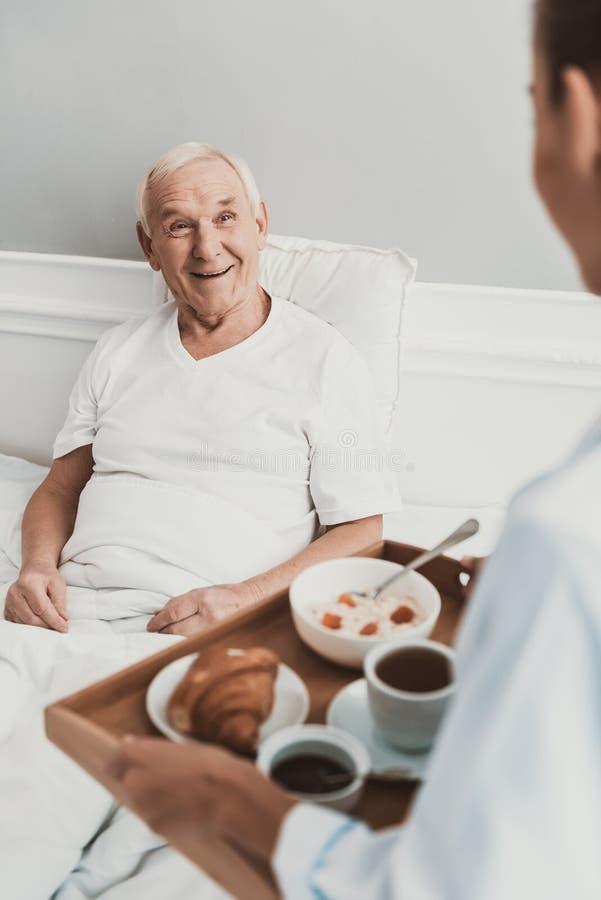 Verpleegster die Lunch geven aan Hogere Patiënt in het Ziekenhuis stock afbeeldingen