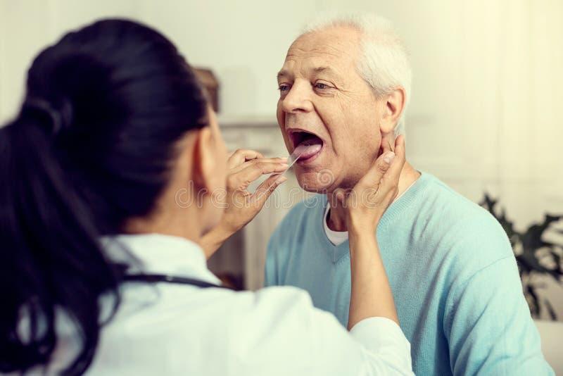 Verpleegster die medische stok gebruiken terwijl het controleren van keel van patiënt royalty-vrije stock afbeelding