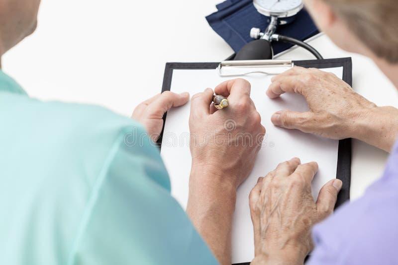 Verpleegster die nota's nemen stock foto's