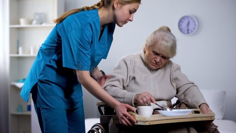 Verpleegster die onsmakelijk dieetdiner dienen aan oude gehandicapte vrouw, die zorg nemen stock fotografie